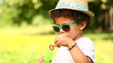 Boy having fun blowing soap bubbles — Stock Video