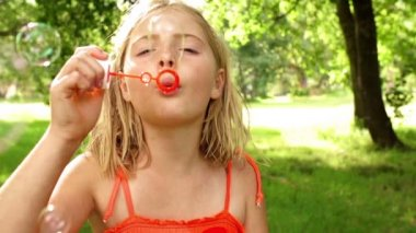 Girl in park blowing bubbles with bubble wand — Stock Video