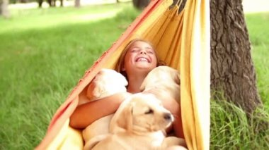 ハンモックで揺れている間ラブラドール子犬を保持している幸せな女の子 — ストックビデオ