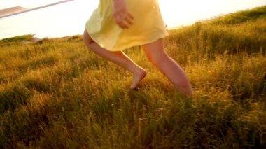 Girl is running through grass at lake — Stockvideo