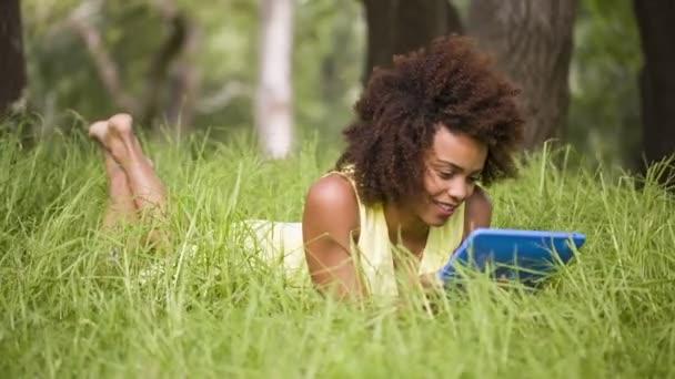 Chica con tableta digital en el parque — Vídeo de stock