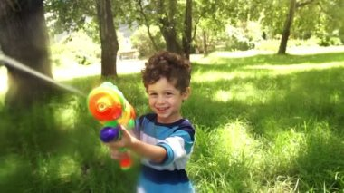 Boy playing with squirt gun — Stock Video
