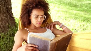 African american woman reading book in a hammock — Stock Video