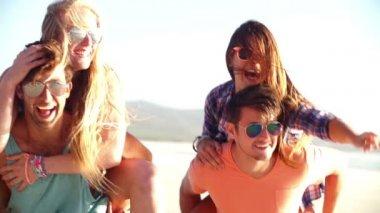 Two couples piggyback on beach — Stockvideo