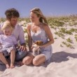 Family and pet dog sitting on beach — Stock Video