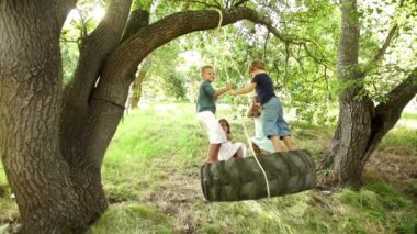 Group of kids swinging on tire — Stock Video