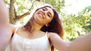 Young woman taking a selfie in the park — Vídeo de Stock