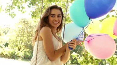 Woman smiling while holding balloons — Stockvideo