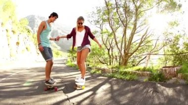 Couple holding hands on skateboard — Stok video