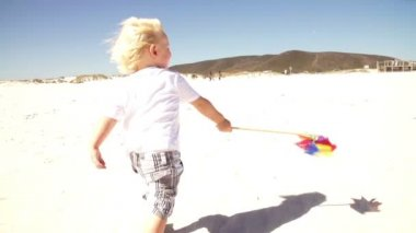 Kid playing with his toy windmill — Vídeo de stock
