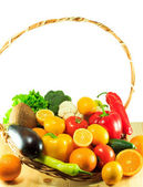 Organic vegetables and fruits in a wooden basket — Stock Photo