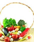 Organic vegetables in a wooden basket on a wooden background — Stock Photo