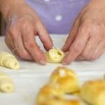Постер, плакат: Baker making mini croissants close up