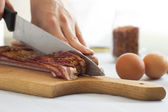 Chef cutting bacon into strips, close up — Stock Photo