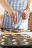 Cook putting spices onto paleo muffins — Stock Photo