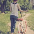 Hipster teenage girl with her vintage bicycle. Rear view — Stock Photo #48927787