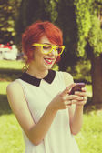 Cute hipster girl text messaging. Retro tones — Stock Photo