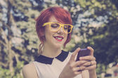 Cute hipster girl text messaging. Retro tones — Stockfoto