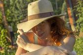 Shy girl in a summer hat enjoying the sun — Stock Photo