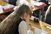 Gros plan d'une écolière écrire quelque chose — Photo