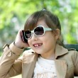 Smiling little girl in talking on cell phone — Stock Photo #49661737