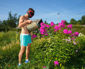 Brutal funny man in helmet watering flowers — Stock Photo