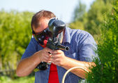 Giant shooter with paintball gun — Stockfoto