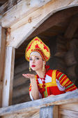 Russian girl in a kokoshnik sends an air kiss — Stockfoto