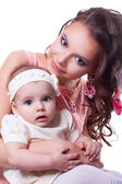 Mother in a pink dress with a daughter 6 months in white dress — Stock Photo