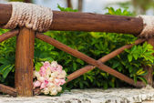 Bouquet of pink roses lay near a wooden fenced — Stock Photo