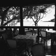 Black and white photo of empty open air restaraunt near sea at sunset — Stock Photo #42895937