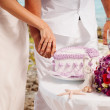 Close-up mid section of a newlywed cutting wedding cake — Stock Photo