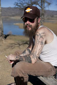 Hipster man with tattoo smokes — Stock Photo
