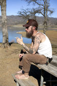 Hipster man with tattoo smokes — Stok fotoğraf