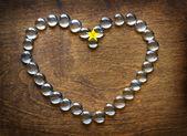Coração de grânulos de vidro sobre a mesa de madeira — Foto Stock