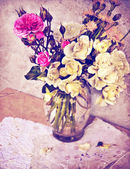 Roses in vase, petals and handmade paper. — Stock Photo