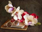 Magnolia blommor med solglasögon och bok — Stockfoto