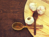 Garlic and wooden spoons — Stock Photo