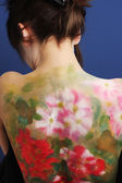 Flowers on back of girl — Stock Photo