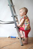 Cute baby girl climbing on a step ladder in domestic room during repair works — Stock Photo