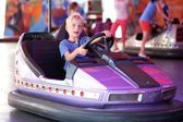 Happy teenager boy rides electric car during fan-fair entertainment — Stock Photo