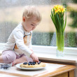 Girl enjoying pancakes sitting on the kitchen — Stock Photo