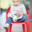 Baby girl sitting indoors on a small red plastic chair — Stok fotoğraf
