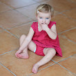 Girl eating cookie sitting cozy on a tiles floor — Stock Photo #42669637