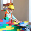 Boy building a house with big plastic construction bricks — Stock Photo #42669645