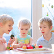 Group of cute children from one family, two twin brothers and their little toddler sister, decorating and painting Easter eggs sitting together in the kitchen on a sunny day. Selective focus on girl. — Stock Photo #42669763