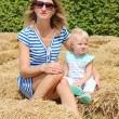 Mother with baby girl sitting together in a middle of a hay labyrinth — Stock Photo