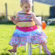 Girl playing with soap bubbles sitting on chair — ストック写真