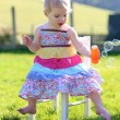 Girl playing with soap bubbles sitting on chair — Stock fotografie