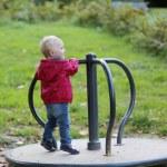Baby girl riding on merry-go-round carousel — Stock Photo #42669907